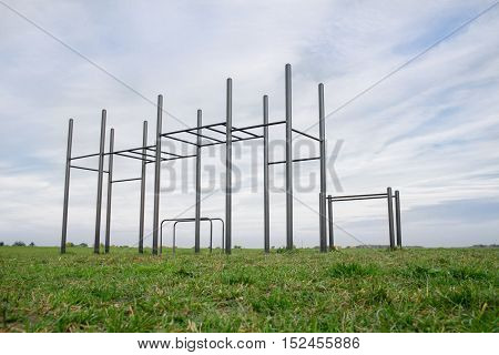 Public training ground in a park. street workout and horizontal bar on green grass.