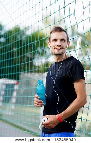 Smiling sporty man listening to music with headphones and holding bottle of water
