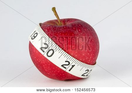 Royal Gala apple with a tape measure. Diet concept.