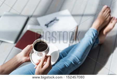 Small pause. Top view of lady sitting barefoot on grey wooden floor and holding full coffee cup.
