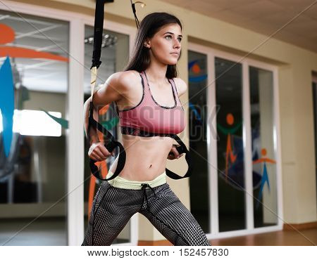 Young Fit Woman Doing Pull-ups Ontrx. Muscular Young Female Athlete Exercising With Trx At Gym.