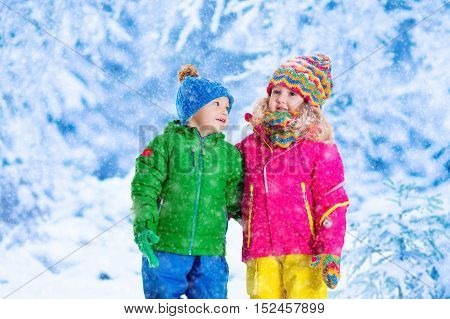 Little girl and boy in colorful hat catching snowflakes in winter park on Christmas eve. Ski vacation for family with children. Kids play outdoor in snowy forest. Children catch snow flake on Xmas.