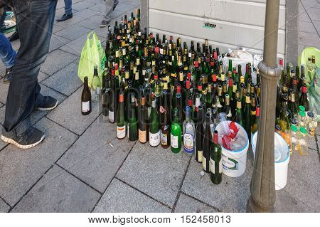 STRASBOURG FRANCE - DEC 15 2013: Multiple wine and beer bottles near glass recycle bin in urban enviroment in the french city of Strasbourg France