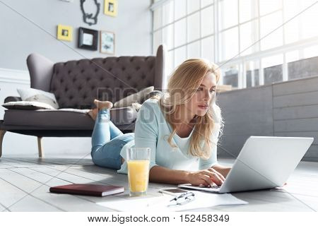 Using social media. Beautiful blond lady lying on wooden floor at home and using her new laptop.