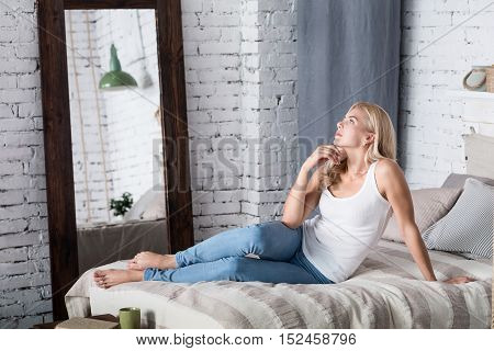 Thought process. Portrait of beautiful blond lady lying on bed barefoot holding her hand at chin and thoughtfully looking up.
