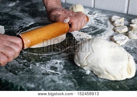 Food crumbly dough from flour on the chef's table with the help of a rolling pin