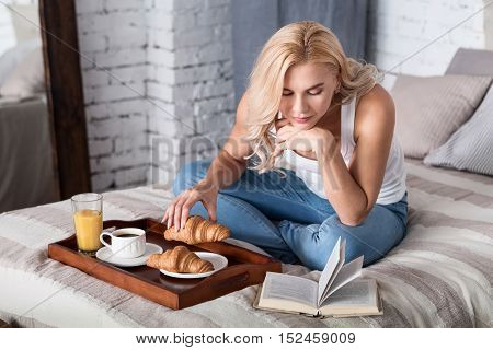 Enjoying book. Beautiful blond woman sitting on her bed and reading book during breakfast.