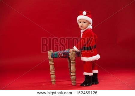 Beautiful little baby celebrates Christmas. New Year's holidays. Baby in a Christmas costume He is sitting on a chair on a red background