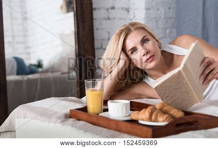 Relaxing moment. Pretty blond lady lying on bed during breakfast time and holding opened book .