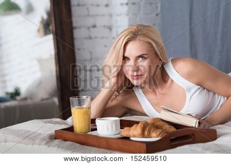 Time to eat. Beautiful blond woman lying on bed with closed book and going to have breakfast.