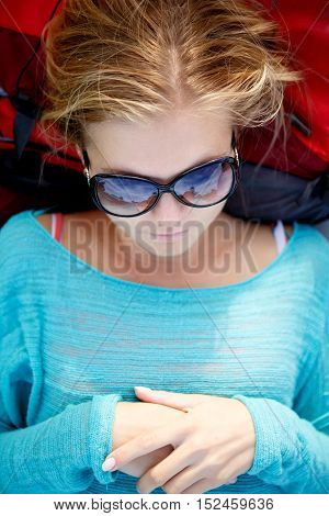 Beautiful blonde woman lying her head on backpack. Her sunglasses reflect the sky
