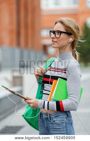 Girl with books and Tablet looks at brick building on street