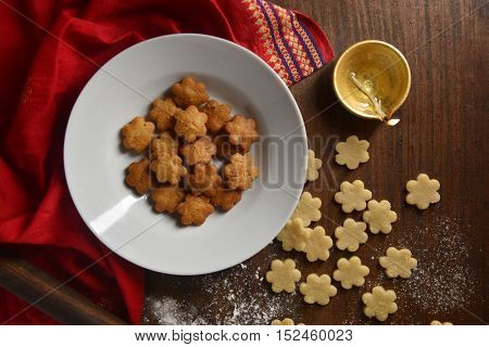 Homemade traditional cookies made during festival of Diwali. A bowl of deep fried cookies with Diya shot from above.