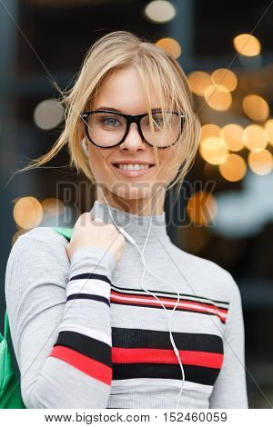 Girl in glasses and striped sweater on background of glass doors with highlights from lights
