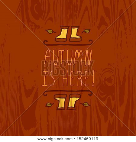 Hand-sketched typographic element with rubber boots, leaves and text on wooden background. Autumn is here