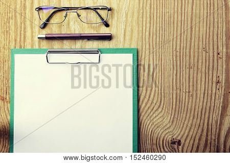background papers and notebooks on a wooden table bright textural