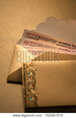 One thousand Indian rupee notes in a decorative golden envelopes. Cash rewards.