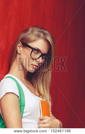 Young woman in glasses stands sideways off red Wall