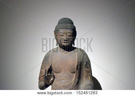 escultura de buda meditando sobre fondo blanco