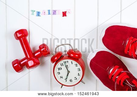 Red sneakers clock and dumbbells on the wooden backgroyund. Training.
