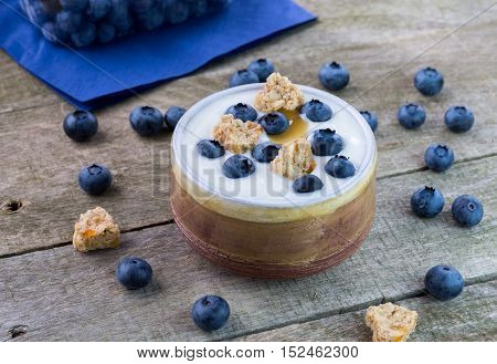 White yogurt with blueberries and cereals in ceramic bowl.