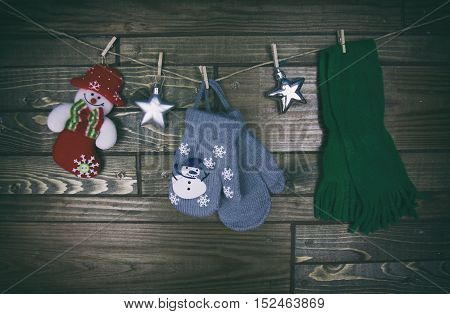 New Year s toys on a wooden background mittens snowman scarf and stars