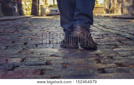 tourist walks on the cobbled pavement urban road