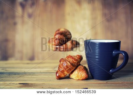 small freshly baked croissant and cup of hot flavored tea on the table