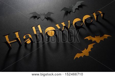 Word Halloween in the dark paper cut and casts a shadow.