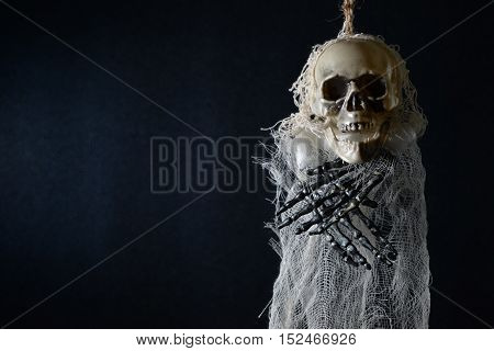Terrible skeleton hanged on a dark blue background.
