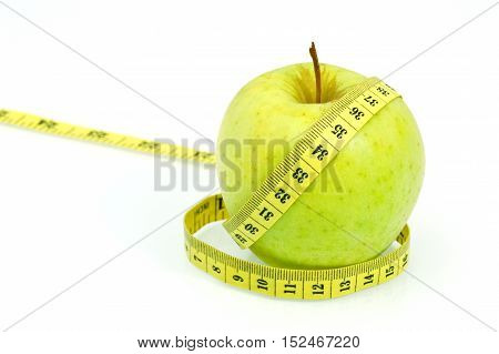 Eating Sour Green Apple Skins Help You Lose Weight . ( Soft focus , lens blur ) Green apple with measuring tape on white background.