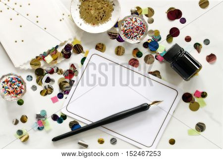 Over head flat lay desktop covered in confetti, party supplies, sprinkles, pen and ink, blank notecard