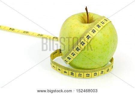 Eating Sour Green Apple Skins Help You Lose Weight. ( Soft focus , lens blur ) Green apple with measuring tape on white background.