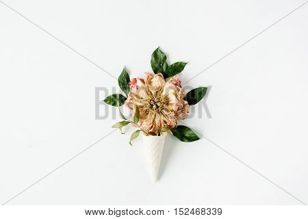 ice cream waffle cone with dried beige peony flower on white background flat lay top view. autumn wallpaper