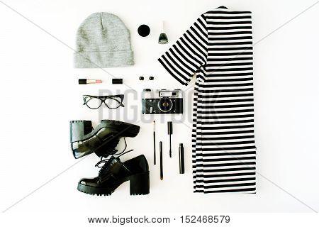 female autumn and winter clothes collage with retro camera accessories and cosmetics on white flat lay top view