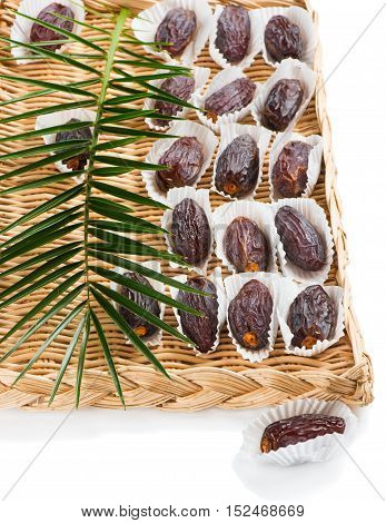 Date fruits (Medjool) with leaf of palm tree in a wicker tray with one on the surface in the foreground isolated on white background.
