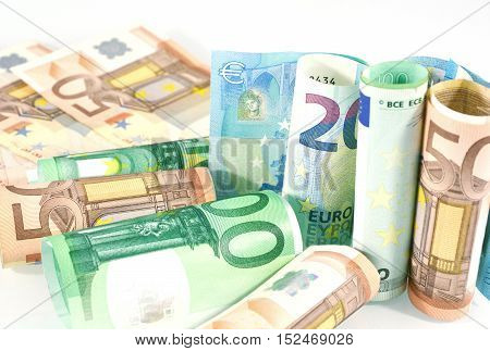 Euro banknotes rolled on a white background.