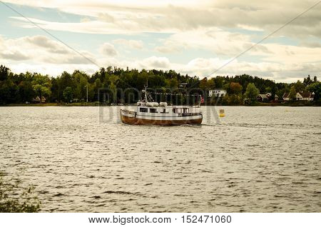 boat floating on norwegian fjord in autumn