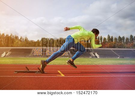 Afro-American man running around the stadium. Young sprinter on the track for jogging