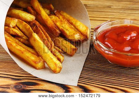 Homemade fast food portion of french fries in paper bag on wood table selective focus