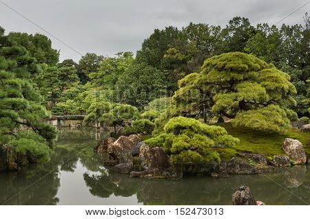 Kyoto Japan - September 19 2016: View on part of the garden of Ninomaru Palace at Nijo Castle. Pond rocks trees and a small bridge. Cloudy sky.