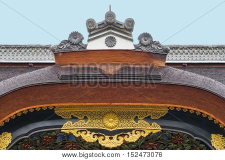 Kyoto Japan - September 19 2016: The central crest of the Kara-Mon gate at the Nijo Castle shows a wooden bow golden trim and wood carvings under a light blue sky.