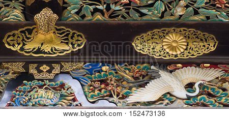 Kyoto Japan - September 19 2016: Closeup of wood carving at Kara-mon gate in Nijo Castle. Crane and golden decorations.