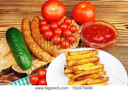 Homemade fast food portion of french fries ketchup grilled sausages and cherry tomato on wooden board