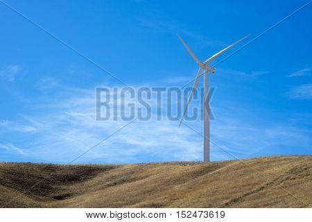 Single wind turbine on top of a hill with blue sky