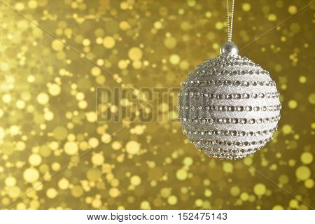 Silver Christmas ball diamond on a gold sparkling background.