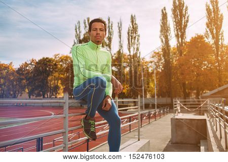 Athletic male runner rests on running track at sports arena