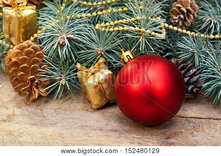 Christmas composition of decorations. Christmas ball, gifts, pine cones and spruce branches on a wooden background