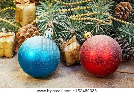 Christmas composition of decorations. Christmas balls, gifts, pine cones and spruce branches on a wooden background