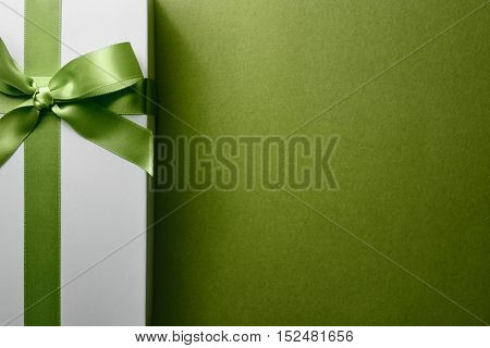 Closeup white gift box on green background